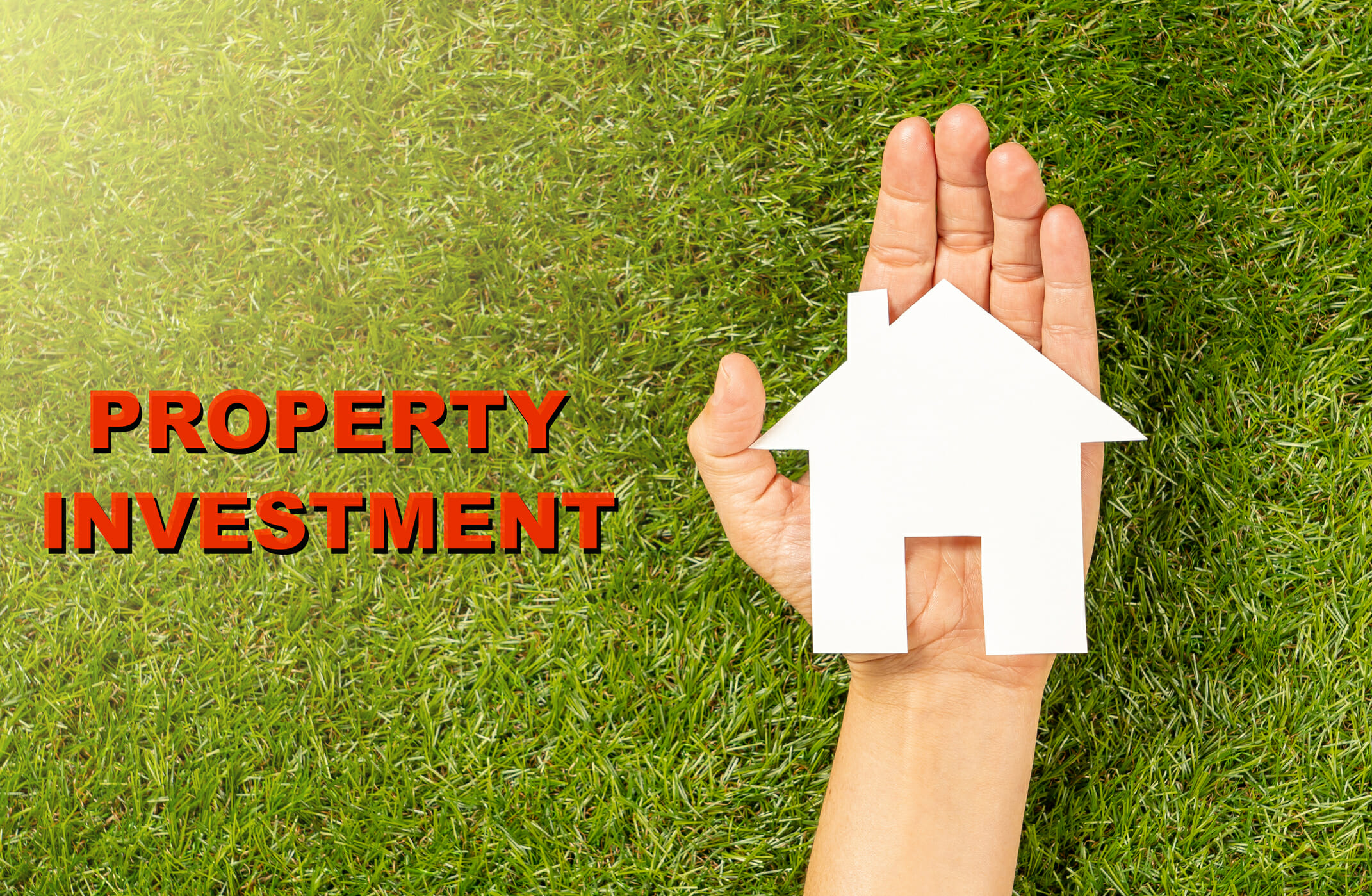 Conceptual picture of woman hand holding white house and Property Investment text written on green grass field top view in Housing Market Real estate buying a home mortgage and loan banking concept.